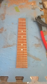 Stage 8: Cut the frets to length and secure them in the fret grooves that were cut earlier. Cut holes for the fret markers and glue them in place.